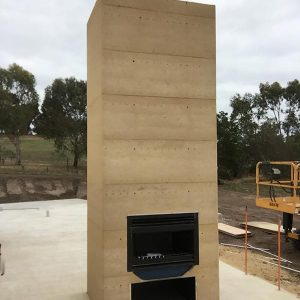 Imagine cool nights around this rammed earth wall and fireplace