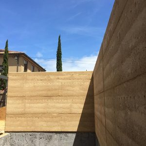 A beautiful rammed earth pool wall