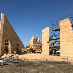These rammed earth walls, under construction, were built by Olnee, the experienced rammed earth builders
